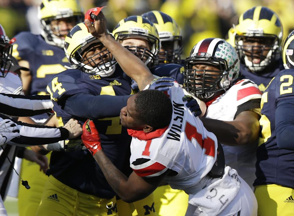 Ohio State's Dontre Wilson (1) is held back by Michigan defensive back Delano Hill (44) as the two teams scuffle during the second quarter of an NCAA college football game in Ann Arbor, Mich., Saturday, Nov. 30, 2013. The third-ranked Buckeyes lost starting right guard Marcus Hall and kick returner Dontre Wilson and the Wolverines lost backup linebacker Royce Jenkins-Stone to ejections. All three players were flagged for unsportsmanlike conduct and had to leave the field after a skirmish. (AP Photo/Carlos Osorio)