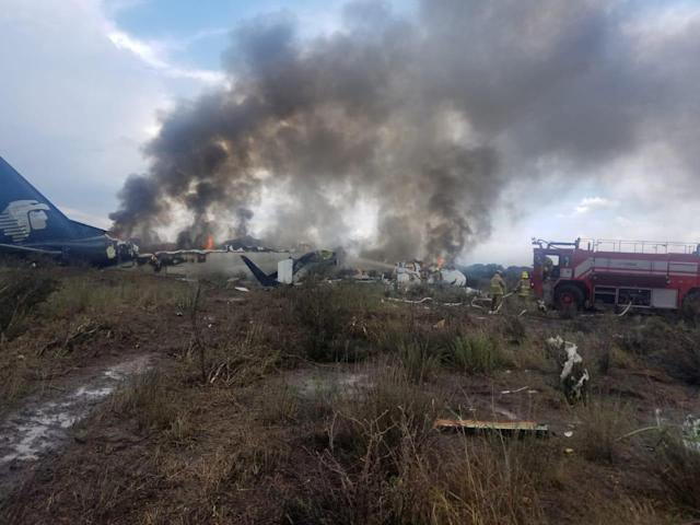 <p>Firefighters douse a fire as smoke billows above the site where an Aeromexico-operated Embraer passenger jet crashed in Mexico's northern state of Durango, July 31, 2018, in this picture obtained from social media. (Photo: Proteccion Civil Durango via Reuters) </p>