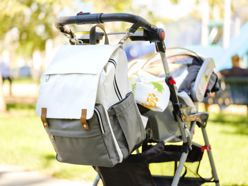 A baby stroller with a diaper bag at the park.