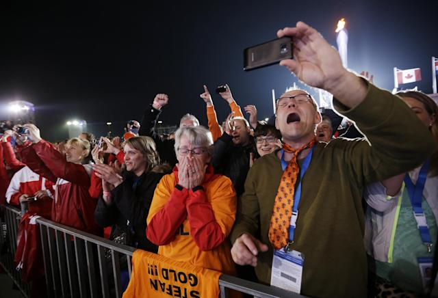 Aart Groothuis and his wife Hendrika Tekelenburg watch their son Stefan Groothuis, of the Netherlands, receive his gold medal in the men's 1000-meter speedskating at the 2014 Winter Olympics, Thursday, Feb. 13, 2014, in Sochi, Russia. (AP Photo/David Goldman)