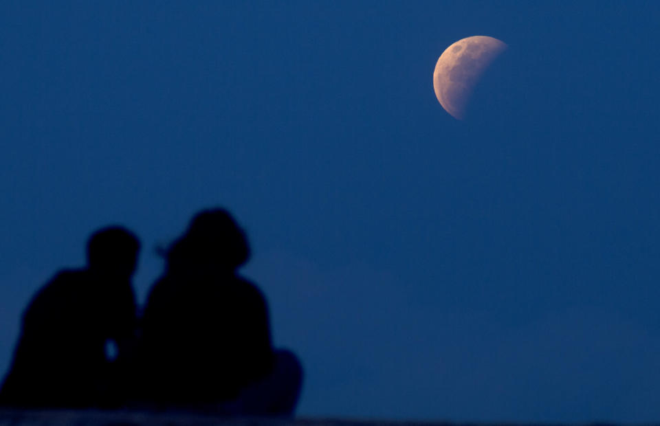 A couple watch the lunar eclipse at Sanur beach in Bali, Indonesia on Wednesday, May 26, 2021. (AP Photo/Firdia Lisnawati)