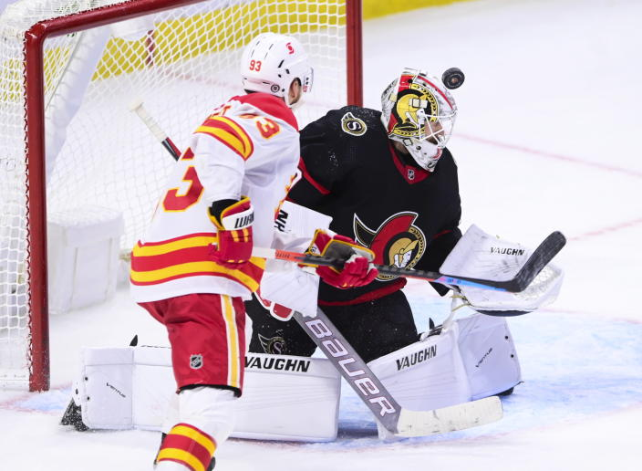 Ottawa Senators goaltender Matt Murray (30) looks for the puck as Calgary Flames centre Sam Bennett (93) moves towards the net during third period NHL hockey action in Ottawa on Monday, March 1, 2021. (Sean Kilpatrick/The Canadian Press via AP)