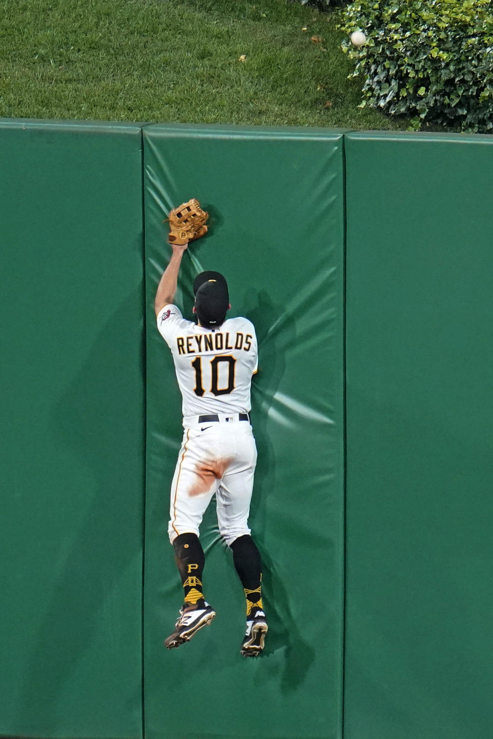 Pittsburgh Pirates center fielder Bryan Reynolds leaps against the center field wall on a a grand slam hit by Cleveland Indians' Cesar Hernandez during the seventh inning of a baseball game in Pittsburgh, Friday, June 18, 2021. (AP Photo/Gene J. Puskar)