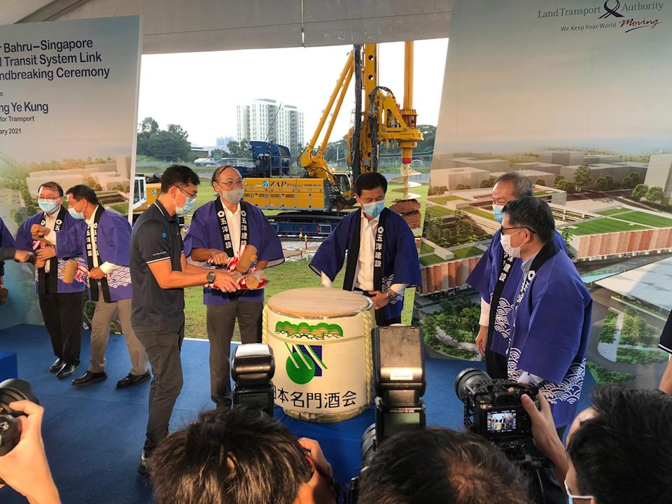 Transport Minister Ong Ye Kung (middle) takes part in a sake barrel breaking ceremony for good luck, at the groundbreaking for the RTS Link Woodlands North Station on Friday, 22 January. The station will be constructed by Penta-Ocean Construction, a Japanese firm. (PHOTO: Nicholas Yong/Yahoo News Singapore)