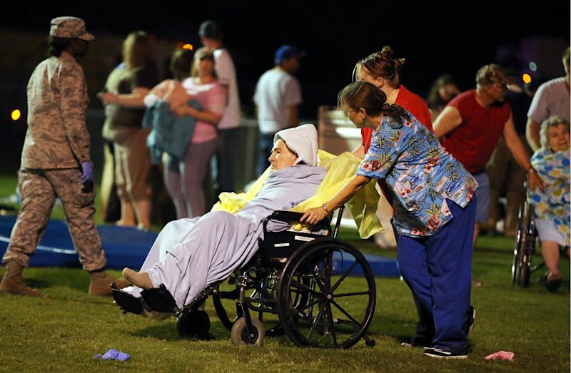 Emergency workers assist an elderly person at a staging area at a local school stadium Wednesday, April 17, 2013, in West, Texas. An explosion Wednesday night at a fertilizer plant near Waco sent flames shooting high into the night sky, leaving the factory a smoldering ruin, causing major damage at nearby buildings and injuring numerous people. (AP Photo/Waco Tribune Herald, Rod Aydelotte)