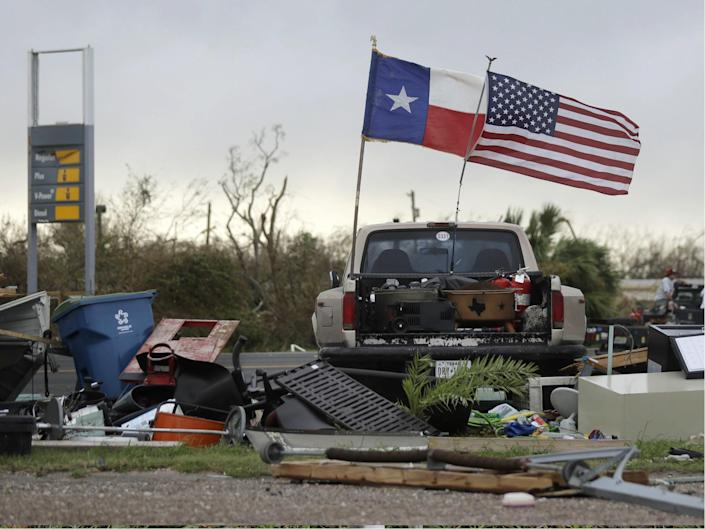 The Texas state flag and American flag wave in the wind over an area of debris left behind in the wake of Hurricane Harvey: AP Photo/Eric Gay