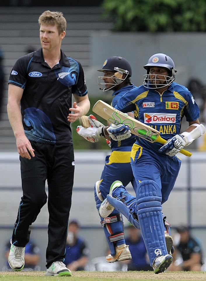 Sri Lankan batsman Tillakaratne Dilshan (R) and teammate Kumar Sangakkara (C) run between wickets as New Zealand cricketer Corey Anderson (L) looks on during the second One Day International (ODI) cricket match between Sri Lanka and New Zealand at the Suriyawewa Mahinda Rajapakse International Cricket Stadium in the southern district of Hambantota on November 12, 2013. AFP PHOTO/ LAKRUWAN WANNIARACHCHI        (Photo credit should read LAKRUWAN WANNIARACHCHI/AFP/Getty Images)
