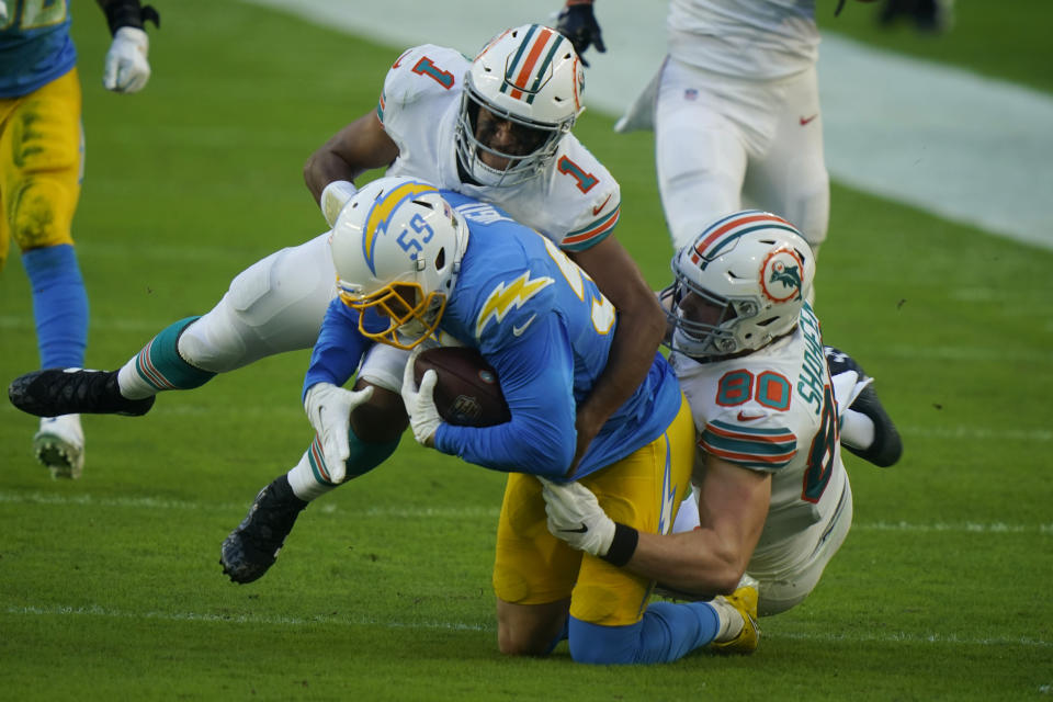 Miami Dolphins quarterback Tua Tagovailoa (1) and tight end Adam Shaheen (80) tackle Los Angeles Chargers outside linebacker Nick Vigil (59) after the Dolphins fumbled the ball, during the first half of an NFL football game, Sunday, Nov. 15, 2020, in Miami Gardens, Fla. (AP Photo/Lynne Sladky)