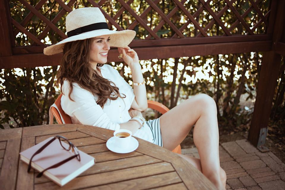 relaxed modern woman in white shirt with cup of coffee, book, hat and eyeglasses sitting at the table in the patio of guest house hotel.