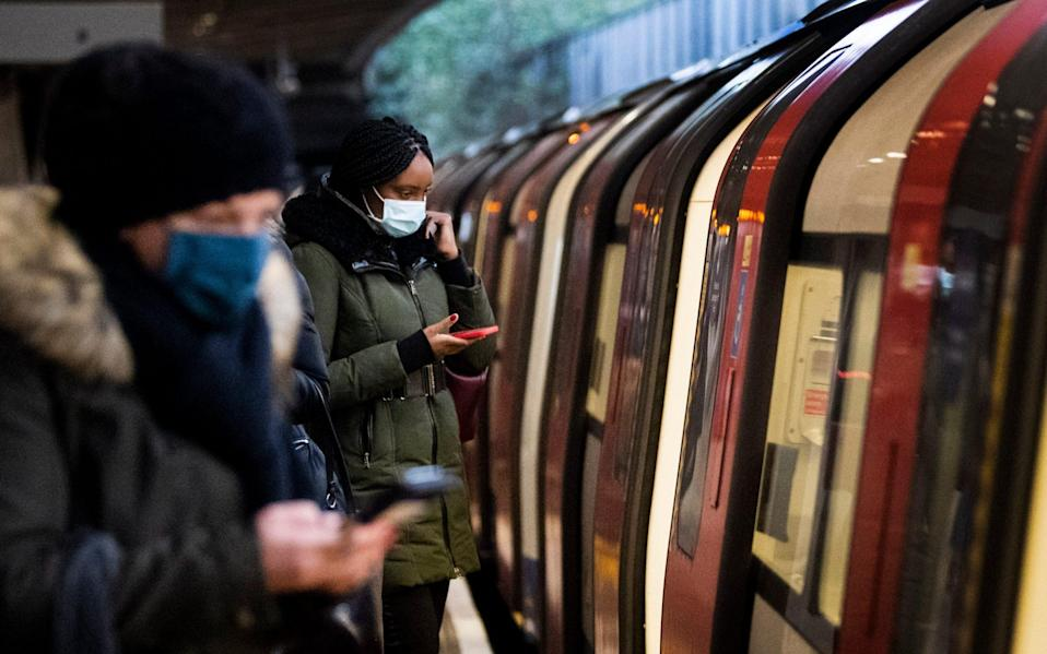 Commuters getting on a Jubilee Line Underground train at Canning Town station during the morning rush hour in London, as England's third national lockdown to curb the spread of coronavirus continues.  - Victoria Jones/PA