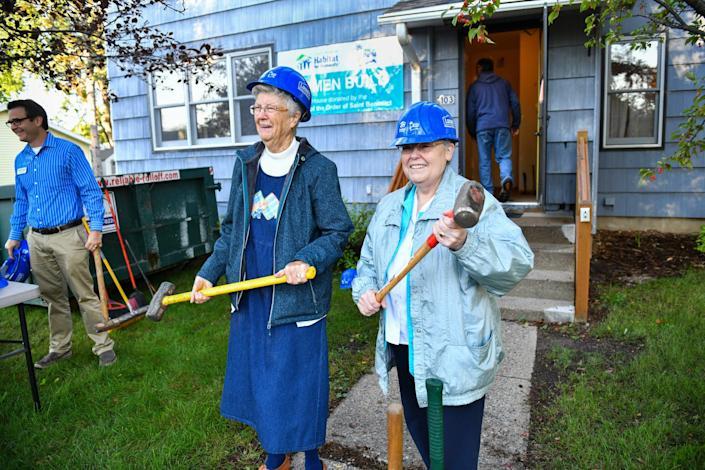 Sister Dorothy Manuel and Sister Karen Streveler pose for photographs with sledgehammers during a kick-off event at a new Habitat for Humanity project house Tuesday in St. Joseph, Minn.. The house was donated to Habitat for Humanity by Sisters of the Order of St. Benedict.