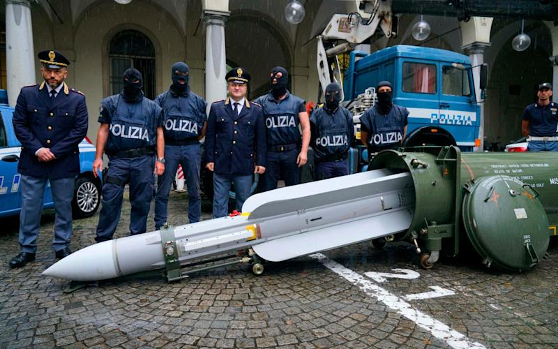 Police stand by a missile seized at an airport hangar near Pavia, northern Italy - ANSA