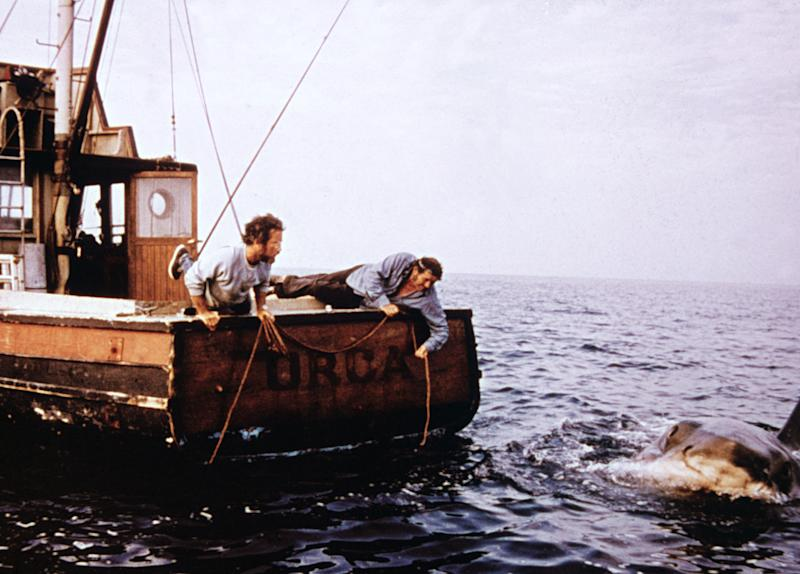 American actor Richard Dreyfuss (L) and British actor Robert Shaw (1927 - 1978) hold ropes while leaning off the back of their boat, 'Orca,' in pursuit of the giant Great White shark in a still from the film, 'Jaws,' directed by Steven Spielberg, 1975. (Photo by Universal Pictures/Fotos International/Courtesy of Getty Images)