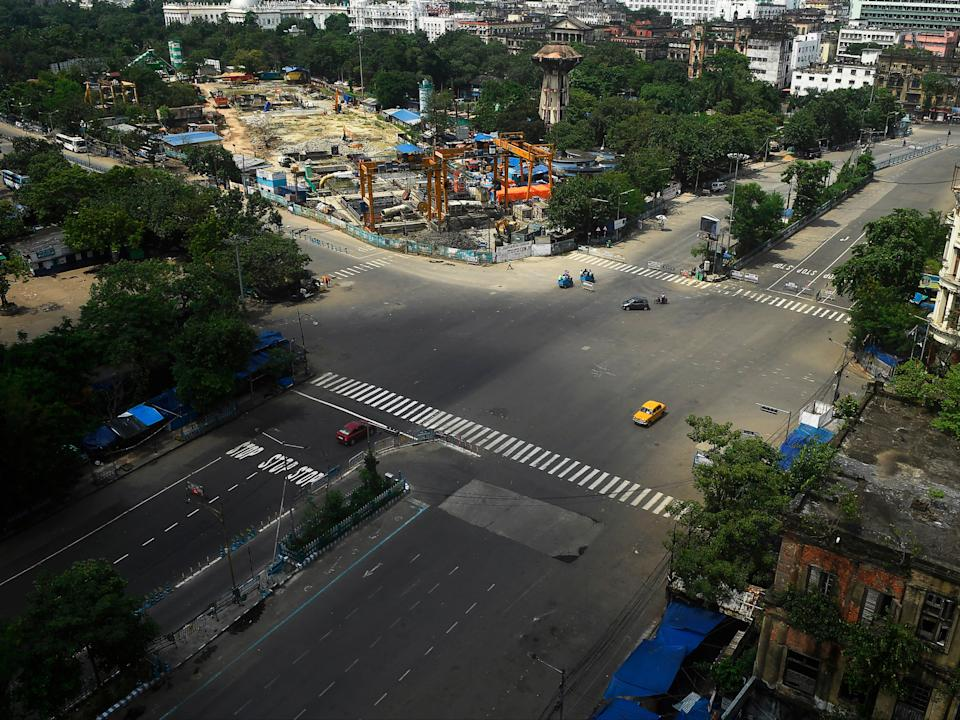 Commuters cross a deserted road during a day-long state-imposed lockdown as a preventive measure against the Covid-19 in KolkataAFP via Getty Images