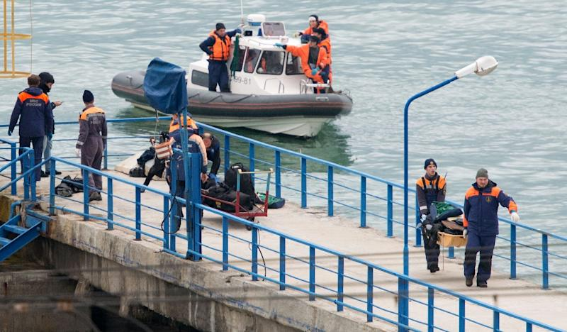 Russian rescuers carry a stretcher with passengers' belongings on a pier in Sochi, after a Russian military plane crashed in the Black Sea on December 25, 2016 (AFP Photo/)