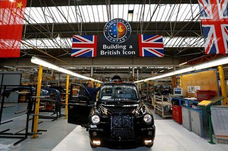 A worker checks a TX4 at the end of the production line at the London Taxi Company in Coventry