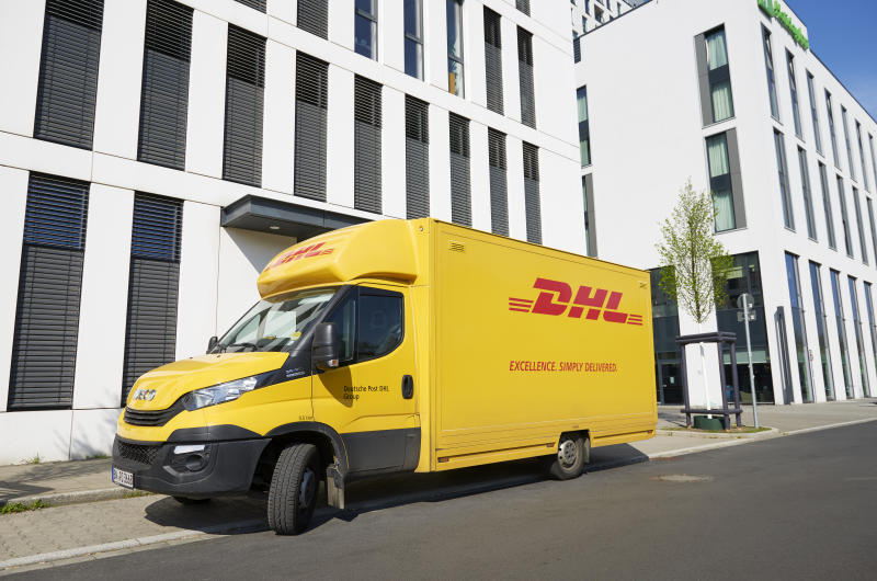 "Duesseldorf, Germany- April 10, 2019: A DHL delivery truck (Iveco) in front of white office buildings at the Duesseldorf quarter ""Le Flair""."