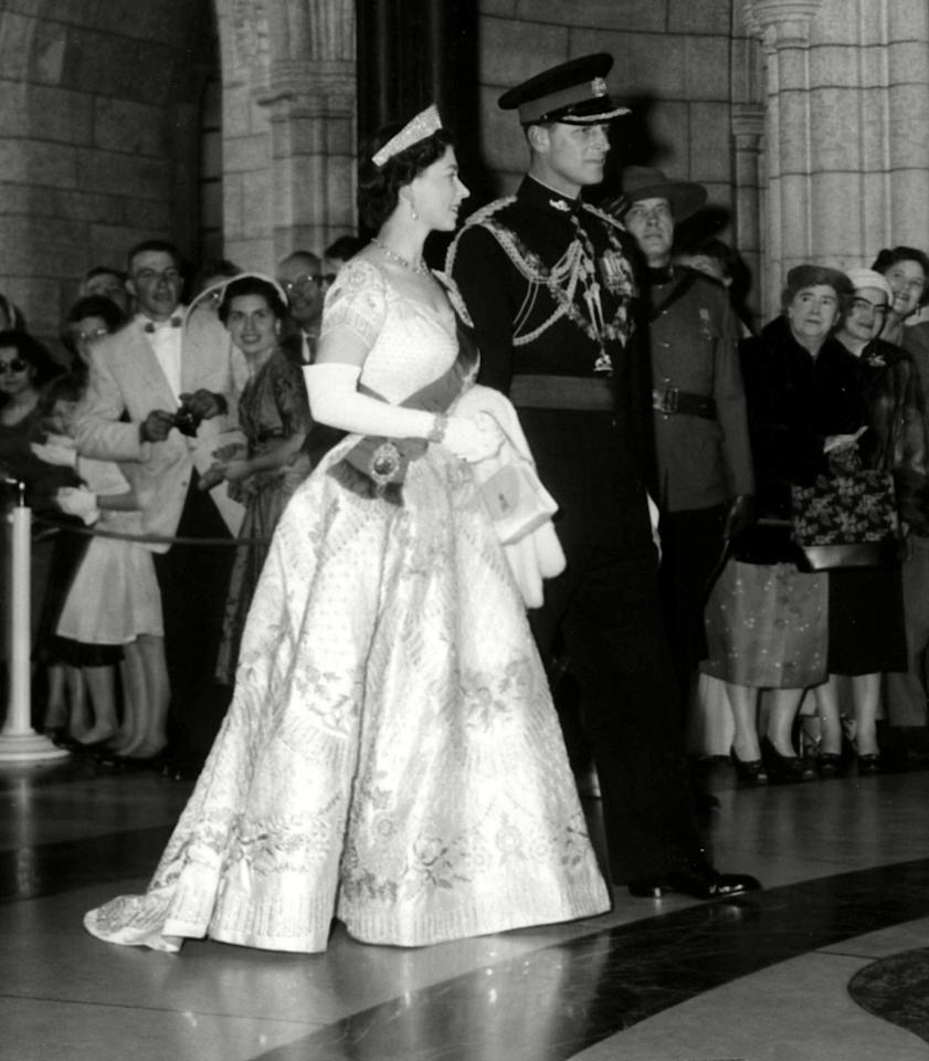 <p>Wearing a dress designed for her by Norman Hartnell for her coronation ceremony, the Queen looked as regal as could be on Prince Philip's arm at the opening of the Canadian parliament in Canada. <i>[Photo: Rex]</i></p>