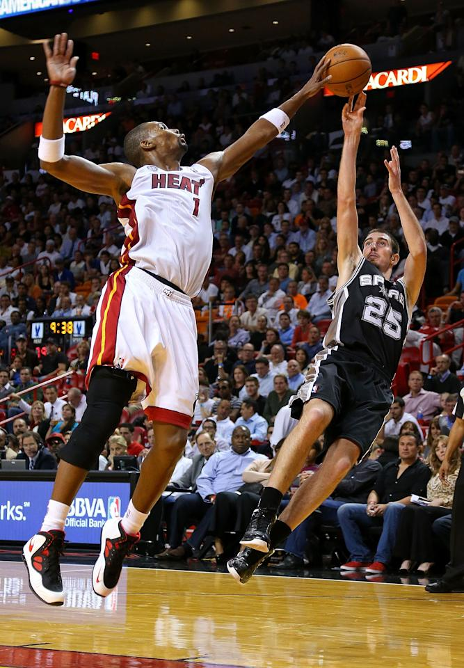 MIAMI, FL - NOVEMBER 29: Chris Bosh #1 of the Miami Heat blocks a shot from Nando de Colo #25 of the San Antonio Spurs during a game  at American Airlines Arena on November 29, 2012 in Miami, Florida.  (Photo by Mike Ehrmann/Getty Images)