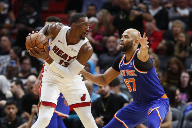 Miami Heat center Bam Adebayo (13) looks for an open teammate past New York Knicks forward Taj Gibson (67) during the first half of an NBA basketball game Friday, Dec. 20, 2019, in Miami. (AP Photo/Wilfredo Lee)