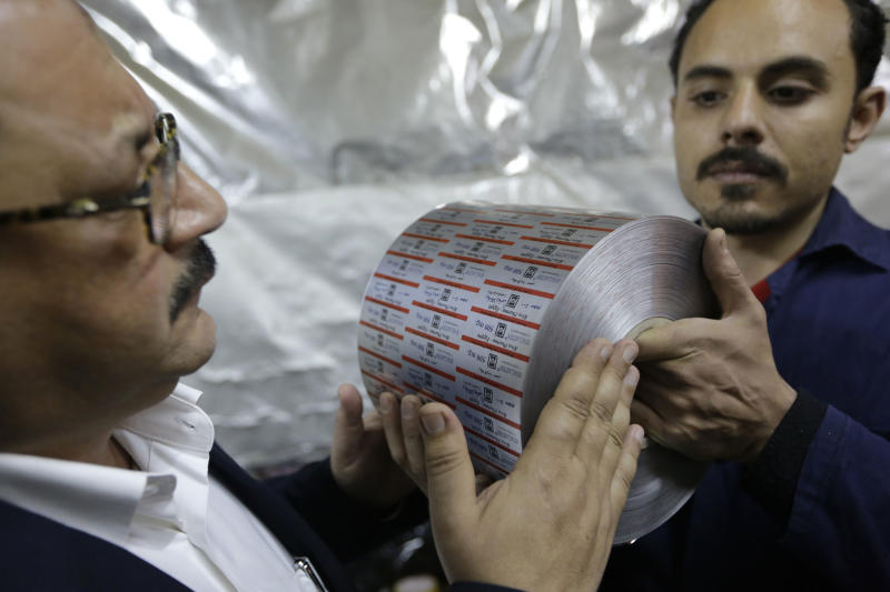 "In this Monday, March 3, 2014 photo, Adel Abd ElSadk, left, examines a final product, aluminum foil printed with the drug name and brand, at his factory financed partly from the Social Development Fund outside Cairo, Egypt. The program, called ""The Project"" in Arabic, highlights entrepreneurship and small business acumen - something experts say is more crucial than ever as Egypt tries to claw its way out of tough economic times. (AP Photo/Amr Nabil)"
