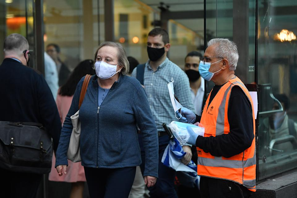 NSW Transport workers hand out face masks at Town Hall train station in Sydney.