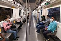 Commuters travel in a carriage of a Yellow Line train after Delhi Metro Rail Corporation (DMRC) resumed services in New Delhi on September 7, 2020. (Photo by PRAKASH SINGH/AFP via Getty Images)