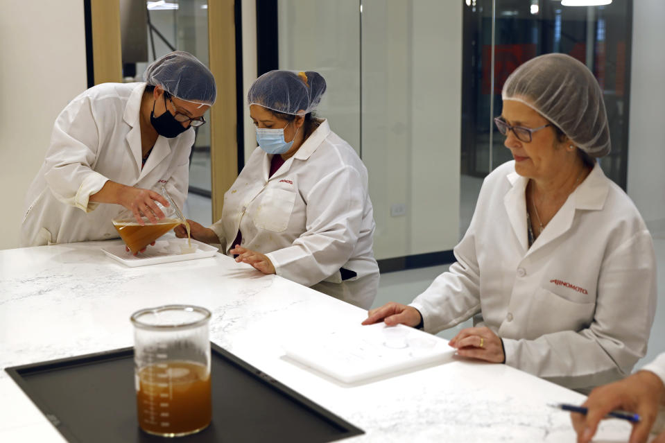 Cathy Legatos, left, associate director of application development of Ajinomoto, a global food and pharmaceutical company, pours a sample to her colleagues at the office dry seasoning lab in Itasca, Ill., Monday, June 7, 2021. In May, Ajinomoto's employees returned to in-person work in a space designed for a post-COVID world. Hallways are wider. Glass panels separate cubicles. The culinary center is wired for virtual presentations. And a cleaning crew comes through twice a day, leaving Post-it notes to show what's been disinfected. (AP Photo/Shafkat Anowar)