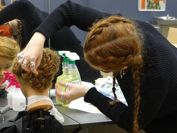 Despite missing in-school practice time, many cosmetology students were able to learn enough to compete in the state Skills USA contests. Here, a competitor creates her own hair design on a mannequin head for judges. (Patrick O'Donnell)