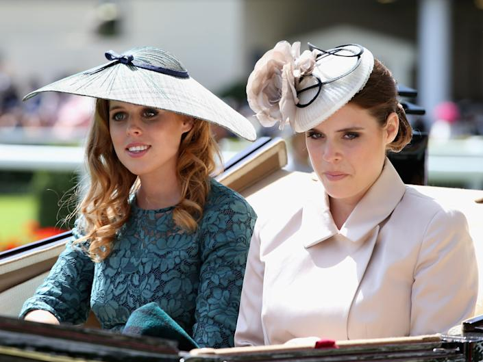Princesses Beatrice and Eugenie ride in a horse-drawn carriage.