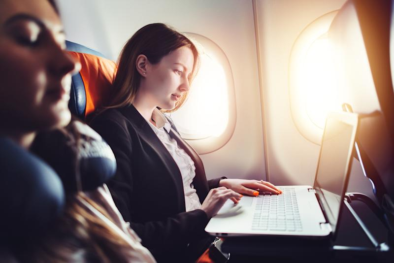 A woman using a laptop on a plane.