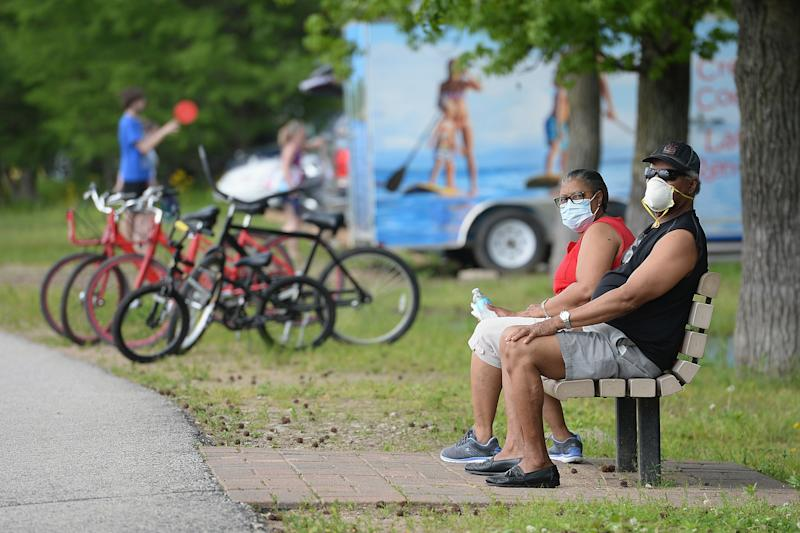 MARYLAND HEIGHTS, MO - MAY 25: A man and woman sit with their masks on at Creve Coeur Lake Park on May 25, 2020 in Maryland Heights, Missouri. Many people flocked to certain area parks to relax and exercise amid COVID-19 social distancing guidelines. (Photo by Michael Thomas/Getty Images)