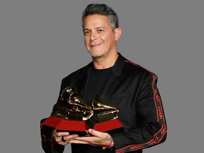 """Alejandro Sanz headshot, as singer, poses in the press room with the awards for record of the year and best pop song for """"Mi Persona Favorita,"""" and best long form music video for """"Lo Que Fui Es Lo Que Soy,"""" at the 20th Latin Grammy Awards, MGM Grand Garden, Las Vegas, Nevada, graphic element on gray"""