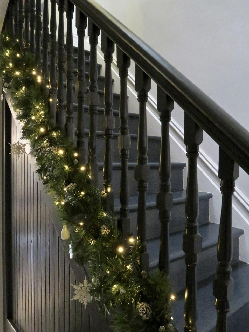 """<p>Here, <a href=""""https://www.ednaandossie.com/festive-stair-garland/"""" rel=""""nofollow noopener"""" target=""""_blank"""" data-ylk=""""slk:Edna & Ossie"""" class=""""link rapid-noclick-resp"""">Edna & Ossie</a> decided to leave the banister empty and glammed up just the base by attaching a garland with ribbons, lights, and some ornaments—<em>et voilà</em>!</p>"""