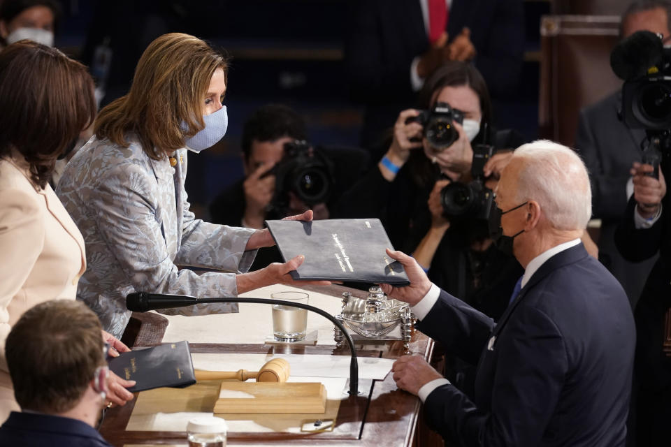 President Joe Biden hands a copy of his speech to House Speaker Nancy Pelosi of Calif., as Vice President Kamala Harris, left, watches as Biden speaks to a joint session of Congress Wednesday, April 28, 2021, in the House Chamber at the U.S. Capitol in Washington. (AP Photo/Andrew Harnik, Pool)