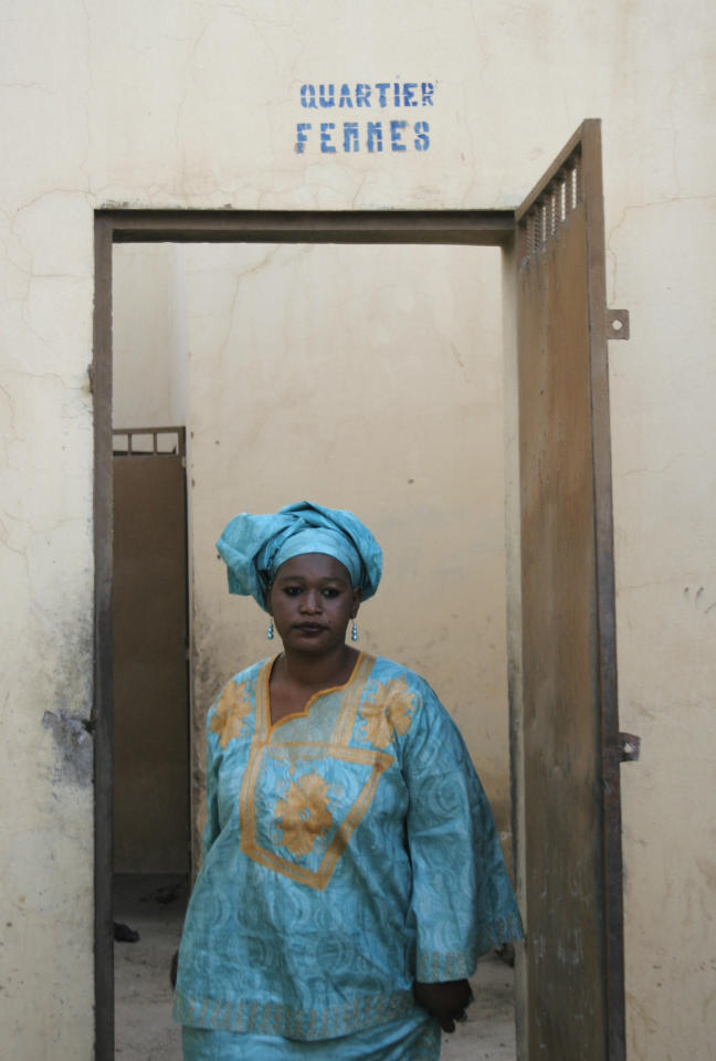 In this Feb. 4, 2013 photo, Salaka Djicke stands at the entrance to the women's jail where she was held for two nights by Islamic police after being caught having a relationship with a married man, in Timbuktu, Mali. Until they were chased out by the French last week, the Islamic extremists who controlled northern Mali since April applied a harsh brand of Shariah in the moderate Muslim region. Djicke was publicly whipped, and at least one other unmarried couple was executed by stoning. (AP Photo/Harouna Traore)
