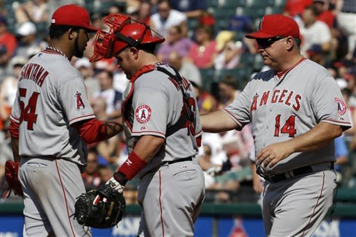 Los Angeles Angels manager Mike Scioscia (14) takes the ball from starting pitcher Ervin Santana (54) in the second inning of a baseball game against the Cleveland Indians, Wednesday, July 4, 2012, in Cleveland. Santana gave up eight runs in 1-1/3 innings. (AP Photo/Mark Duncan)
