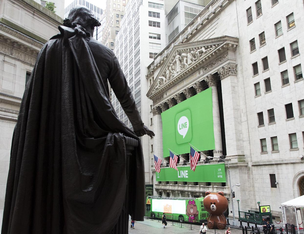 A statue of George Washington overlooks the New York Stock Exchange, Thursday, July 14, 2016, in New York. Japanese messaging app Line has its IPO Thursday at the exchange. Though little known in the U.S., Line has enjoyed a quick surge to popularity in Japan, filling an important communications hole after a devastating earthquake and tsunami in 2011 damaged phone infrastructure. In its home country, Line has more users than Facebook or Twitter. (AP Photo/Mark Lennihan)