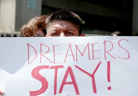 FILE PHOTO - Supporter of the Deferred Action for Childhood Arrivals program, Alex Hernandez, holds a sign during a rally in Los Angeles, California