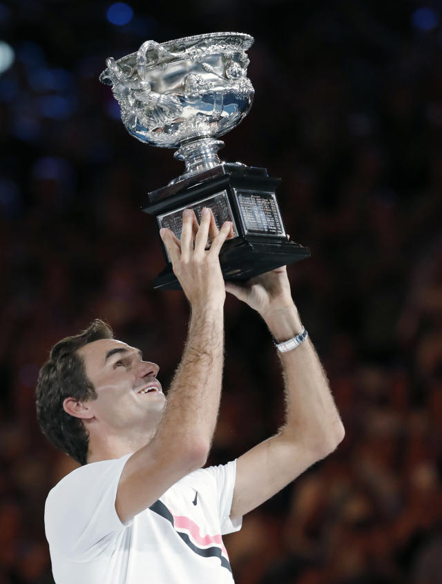 FILE - In this Jan. 28, 2018, file photo, Switzerland's Roger Federer holds up his trophy after defeating Croatia's Marin Cilic in the men's singles final at the Australian Open tennis championships in Melbourne, Australia. Serena Williams, owner of a professional-era-record 23 Grand Slam singles titles, and Federer, owner of a men's-record 20, are both 37 years old, far closer to the ends of their careers than anyone with a stake in the sport would care to think about. (AP Photo/Vincent Thian, File)