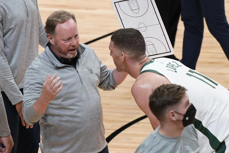 Milwaukee Bucks coach Mike Budenholzer talks to center Brook Lopez (11) during the second half of Game 3 of an NBA basketball first-round playoff series against the Miami Heat, Thursday, May 27, 2021, in Miami. (AP Photo/Marta Lavandier)