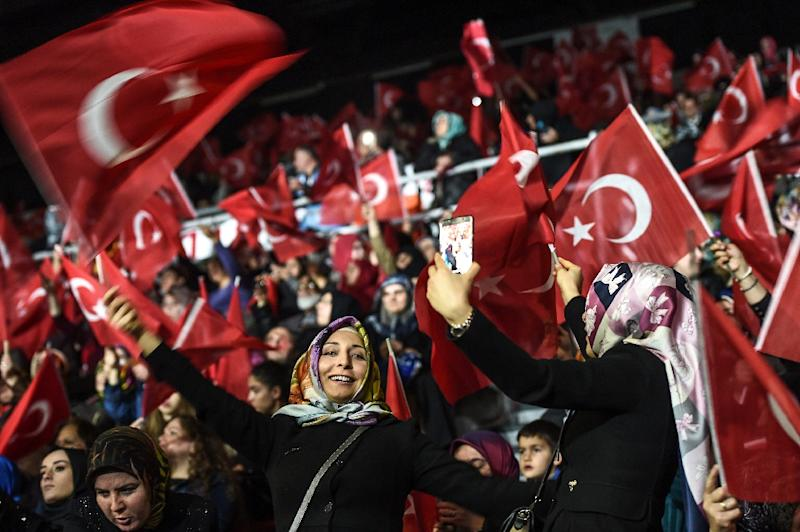 Women wave Turkish national flags during an election rally in Istanbul, on March 5, 2017