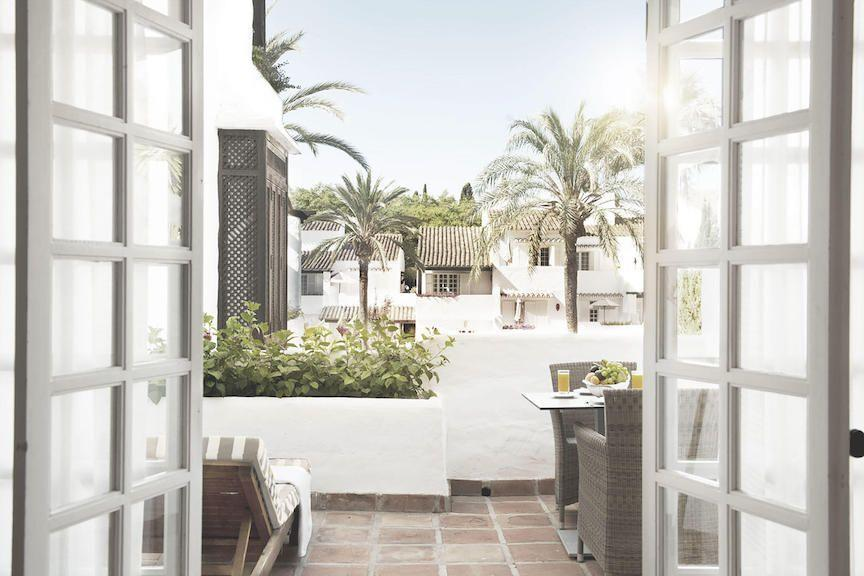 """<p>White may not seem like the first choice for creating a more positive space, but if your space is full of natural light, as shown here at a suite in <a href=""""https://www.puenteromano.com/"""" rel=""""nofollow noopener"""" target=""""_blank"""" data-ylk=""""slk:Puente Romano"""" class=""""link rapid-noclick-resp"""">Puente Romano</a> in Marbella, Spain, it can help you achieve a sense of calm. It also makes a dreamy backdrop for letting your favorite plants shine. </p>"""