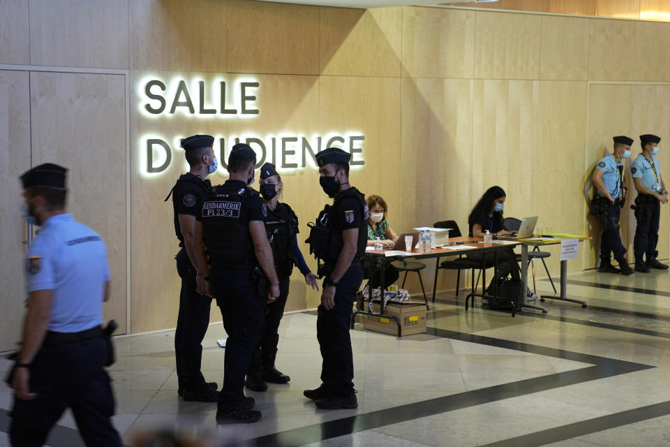 Security forces guard the special courtroom built for the 2015 attacks trial, Wednesday, Sept. 8, 2021 in Paris. France on Wednesday will begin the trial of 20 men accused in the Islamic State group's 2015 attacks on Paris that left 130 people dead and hundreds injured. Among the plantiffs are nearly 1,800 victims, including survivors who suffered physical or psychological harm and families whose loved ones died that night. A total of 330 lawyers are representing them and the defendants. (AP Photo/Michel Euler)