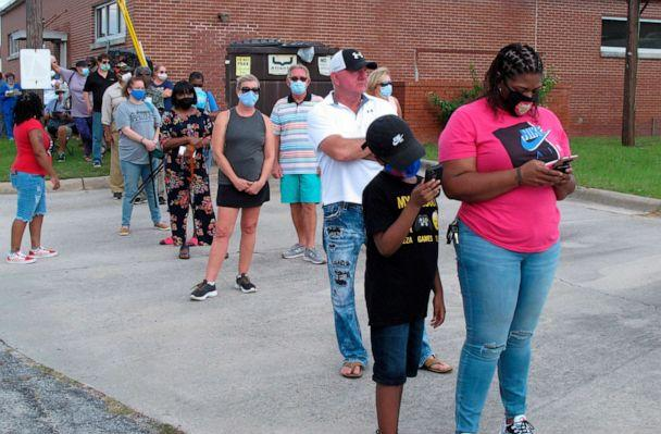 PHOTO: Voters wearing masks wait in line to vote early outside the Chatham County Board of Elections office in Savannah, Ga., Oct. 14, 2020. (Russ Bynum/AP)