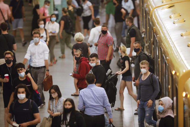 People with face masks leave a public transport train at the Alexanderplatz train station in Berlin, Germany, Friday, Aug. 14, 2020. Wearing face masks to protect against the coronavirus is mandatory on public transport in the German capital. (AP Photo/Markus Schreiber)