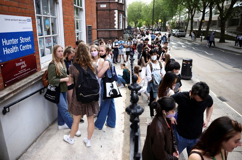 FILE PHOTO: People queue outside a vaccination centre for young people and students at the Hunter Street Health Centre, amid the coronavirus disease (COVID-19) outbreak, in London
