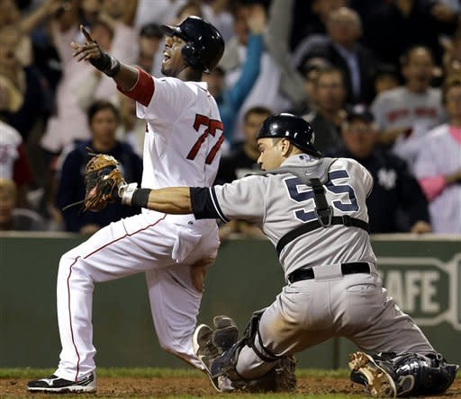 Boston Red Sox's Pedro Ciriaco (77) reacts after scoring the winning run on a single by Jacoby Ellsbury as New York Yankees catcher Russell Martin shows the ball to the umpire during the ninth inning of a baseball game at Fenway Park in Boston, Tuesday, Sept. 11, 2012. The Red Sox won 4-3. (AP Photo/Elise Amendola)