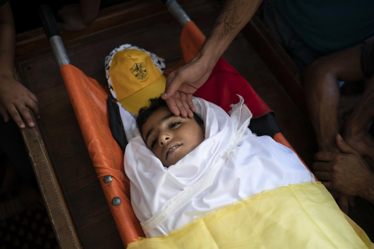 """In this Sept. 15, 2018 photo, Palestinians mourn over the body of 11-year-old Shady Abdel-al during his funeral in Beit Lahiya, northern Gaza Strip. Though the Health Ministry initially reported Abdel-al was shot by Israeli fire, the Israeli army claimed he was accidentally struck by a rock thrown by protesters. Two Gaza rights groups say he died after being hit """"with a solid object."""" (AP Photo/Felipe Dana)"""