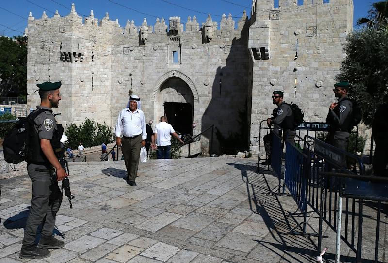 A Palestinian man walks past members of the Israeli security forces standing guard at the Damascus Gate in east Jerusalem on May 31, 2017 (AFP Photo/AHMAD GHARABLI)